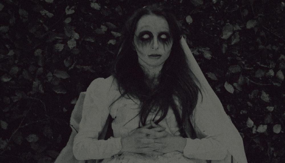 dead women wearing a wedding dress, veil, holding flowers.
