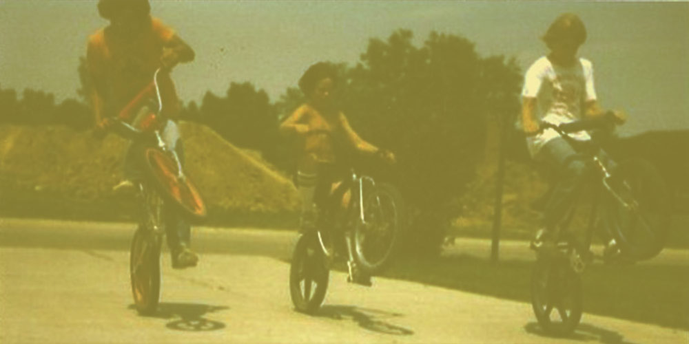 Three kids doing wheelies on bikes under a clear blue sky