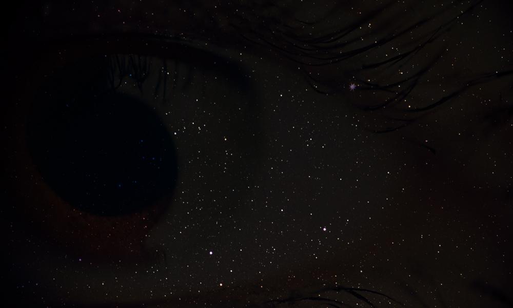 Eyes set back behind dark sky/stars